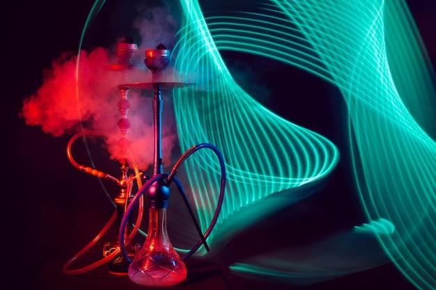 Dois narguilés esfumaçados com frascos de vidro com água e carvão shisha com iluminação neon verde vermelha em um fundo preto