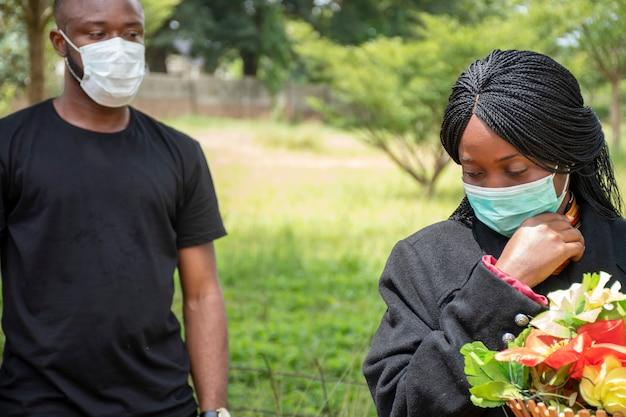 Dois negros em luto pelos perdidos devido ao coronavírus, usando máscaras faciais, distanciamento físico