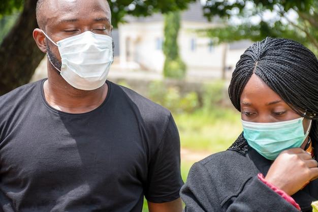 Dois negros em luto pelos perdidos devido ao coronavírus, usando máscaras faciais