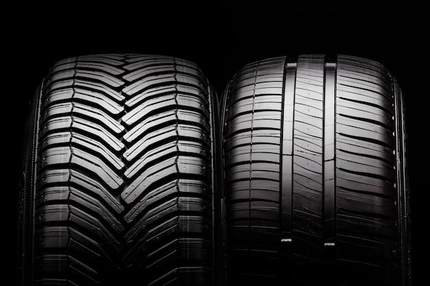 Dois novos pneus de verão e pneus para todas as estações em uma parede preta.