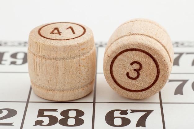 Dois números de barril de madeira e um cartão para um jogo de loteria em um fundo branco. vista de perto