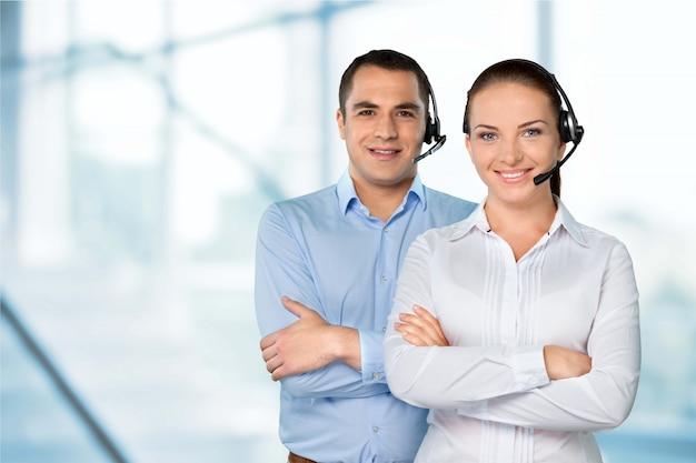 Dois operadores de chamada no fone de ouvido no fundo