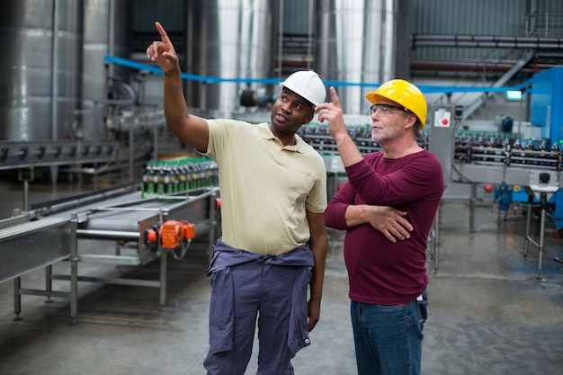 Dois operários apontando para cima enquanto discutia juntos