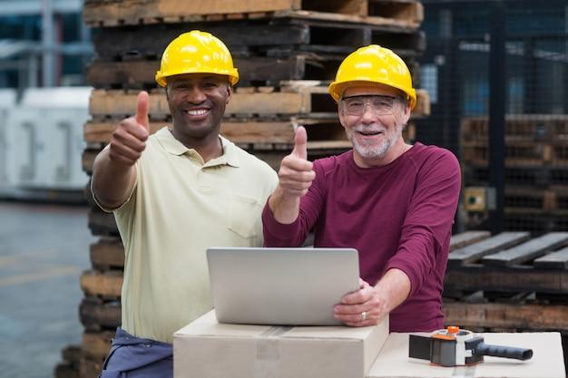 Dois operários com laptop aparecendo os polegares na planta de produção de bebidas