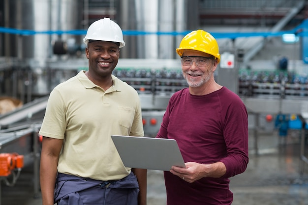 Dois operários com laptop sorrindo na fábrica de bebidas