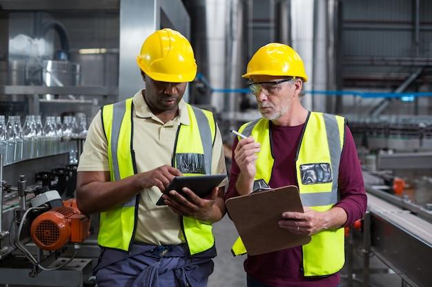 Dois operários com prancheta e tablet digital trabalhando na fábrica