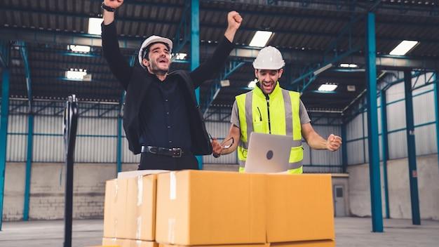 Dois operários comemoram o sucesso juntos na fábrica ou no depósito. conceito de realização do trabalho da indústria.
