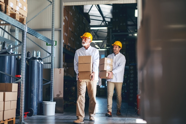 Dois operários em uniformes brancos e capacetes amarelos nas cabeças transferindo caixas pesadas no depósito.