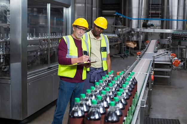 Dois operários monitorando garrafas de bebida gelada na fábrica