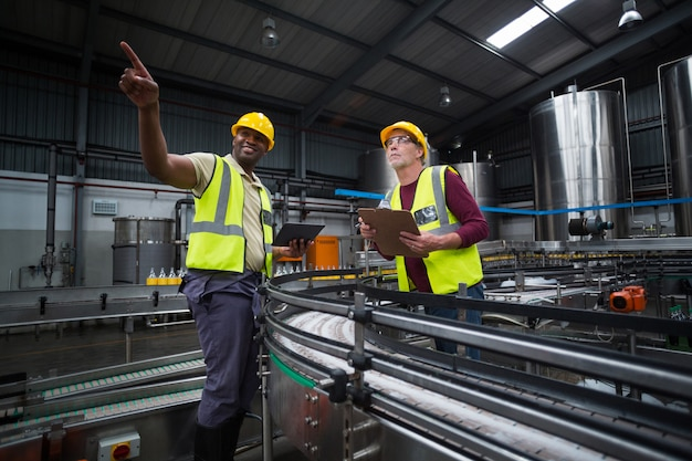 Dois operários olhando para cima na fábrica