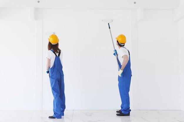 Dois operários pintando parede branca