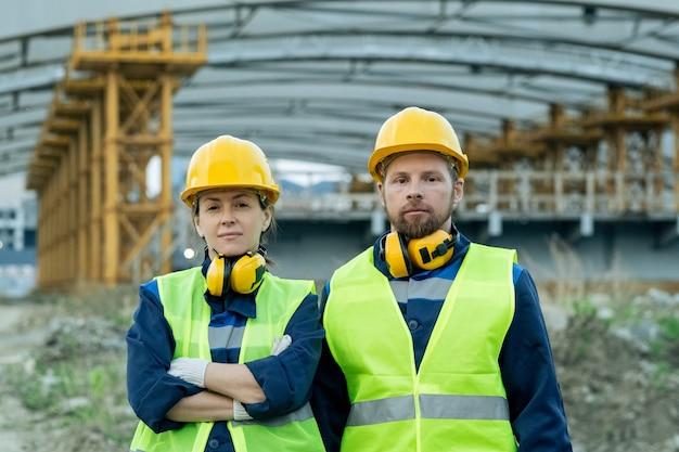 Dois operários sérios de uniforme e capacetes, um ao lado do outro