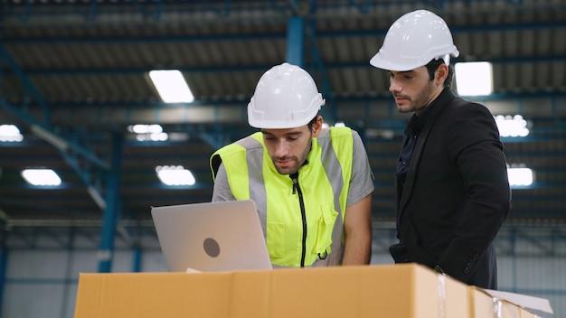 Dois operários trabalhando e discutindo o plano de manufatura na fábrica. conceito de indústria e engenharia.