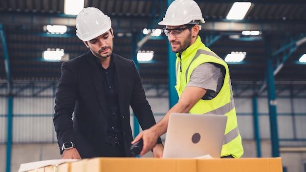 Dois operários trabalhando e discutindo o plano de manufatura na fábrica