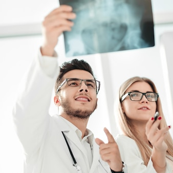 Dois ortopedistas observando a radiografia do paciente