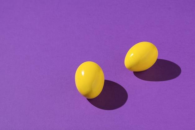 Dois ovos amarelos brilhantes sobre um fundo roxo.