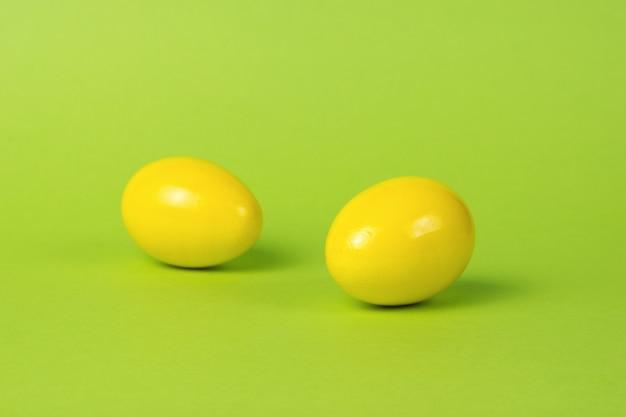Dois ovos amarelos brilhantes sobre um fundo verde.