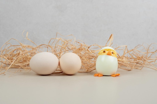 Dois ovos de galinha branca fresca com brinquedo de galinha e feno.