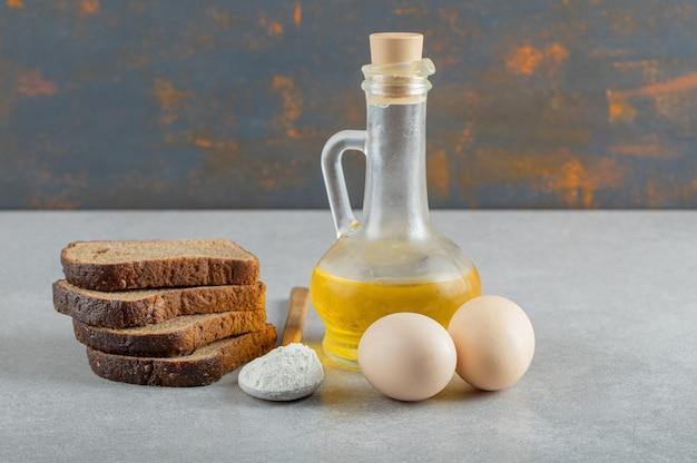 Dois ovos de galinha com fatias de pão e uma garrafa de óleo.