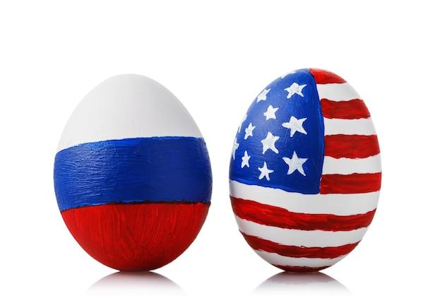 Dois ovos de páscoa pintados com as cores das bandeiras da rússia e da américa isoladas na superfície branca