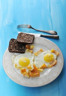 Dois ovos fritos com pimenta e duas fatias de pão de centeio em um prato, faca e garfo em uma superfície de madeira azul