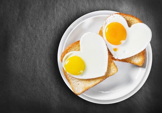 Dois ovos fritos em forma de coração e torradas fritas