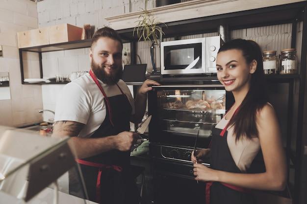 Dois padeiros profissionais estão de pé perto do forno.
