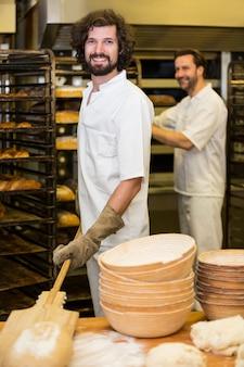 Dois padeiros sorriso que prepara o pão na cozinha da padaria