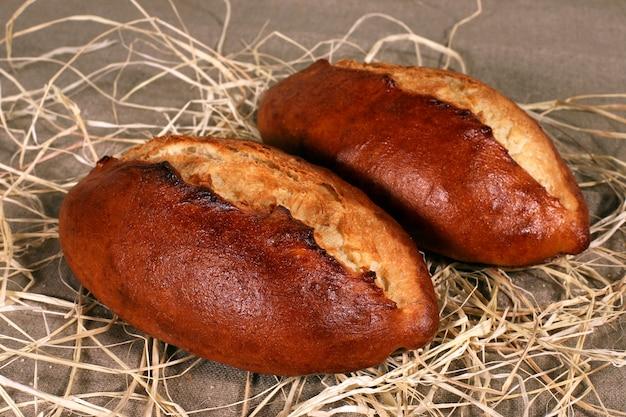 Dois pães brancos em palha sobre toalha de mesa de linho cinza