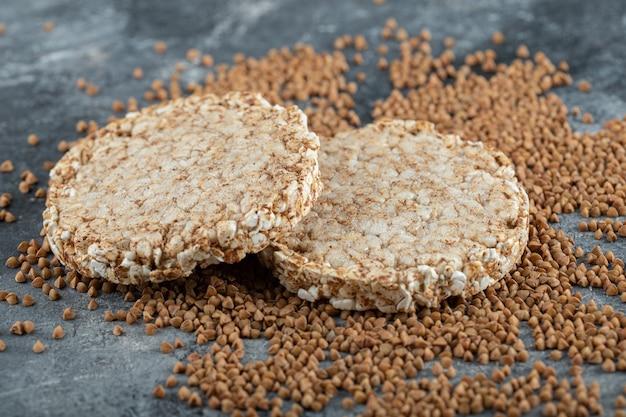 Dois pães crocantes e trigo sarraceno cru na superfície de mármore