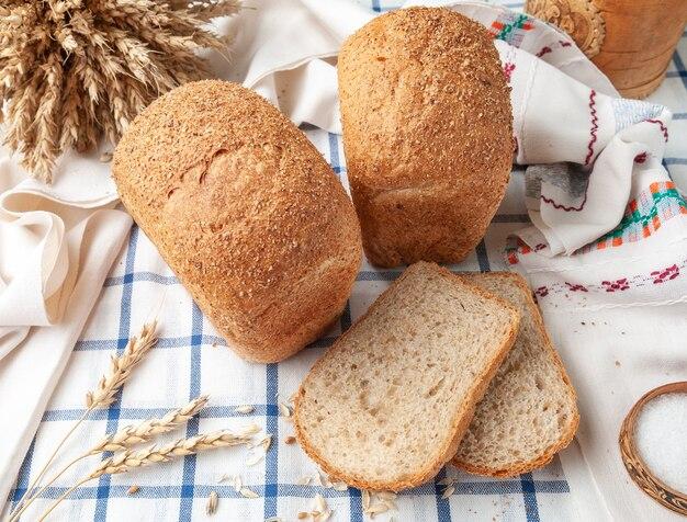 Dois pães de farelo de pão em uma toalha de mesa listrada de azul branco na toalha de mesa estão duas fatias de espigas de trigo e grãos vista de cima estilo country