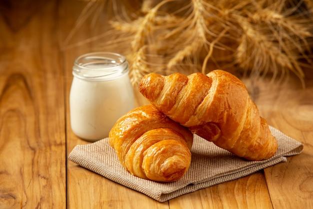 Dois pães e leite colocam um copo no velho piso de madeira.