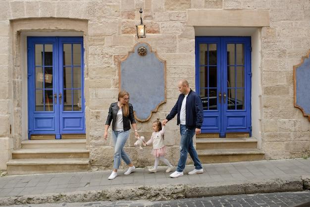 Dois pais com uma filha pequena andam pelas ruas da cidade velha.