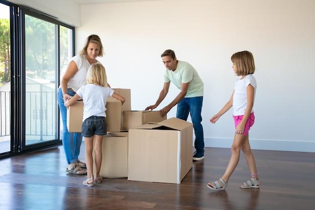 Dois pais e duas meninas abrindo caixas e desempacotando coisas em seu novo apartamento vazio