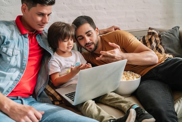 Dois pais e seu filho curtindo o tempo juntos enquanto assistiam a um filme no sofá em casa. conceito de família.