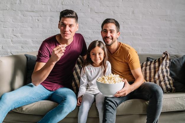 Dois pais e sua filha curtindo o tempo juntos enquanto assistiam a um filme no sofá em casa. conceito de família.