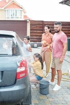Dois pais olhando para os filhos ajudando-os a lavar o carro ao ar livre