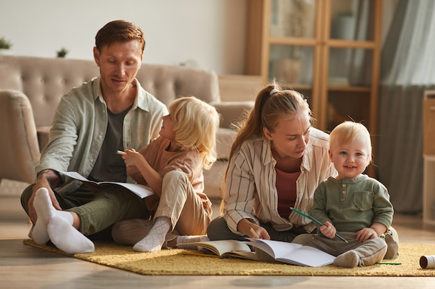 Dois pais sentados no chão lendo um livro para seus filhos pequenos na sala de estar de casa