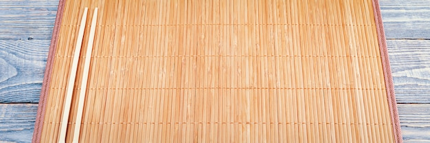 Dois palitos de madeira em uma esteira de bambu