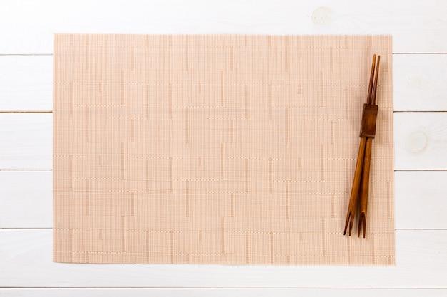 Dois palitos de sushi com esteira de bambu marrom vazia ou placa de madeira na vista superior de madeira branca com copyspace. fundo vazio comida asiática