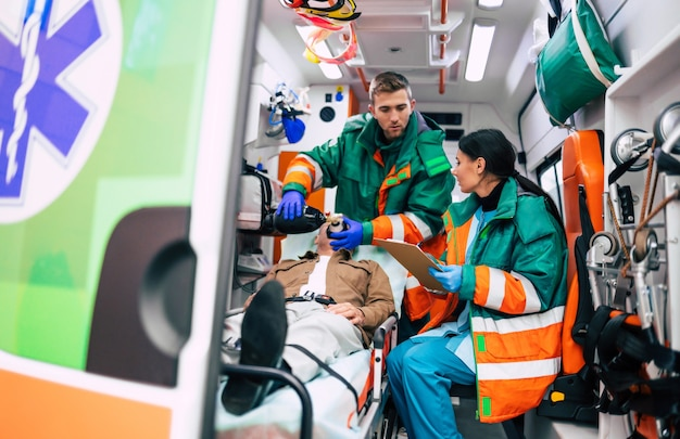 Dois paramédicos profissionais em uma ambulância com um paciente na maca