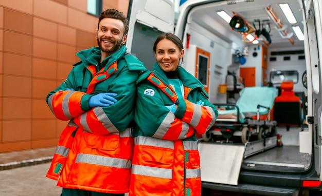 Dois paramédicos uniformizados estão de braços cruzados em frente a uma clínica e a uma ambulância moderna.