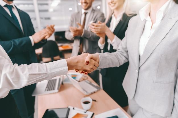 Dois parceiros, apertando as mãos, enquanto outros colegas aplaudem.