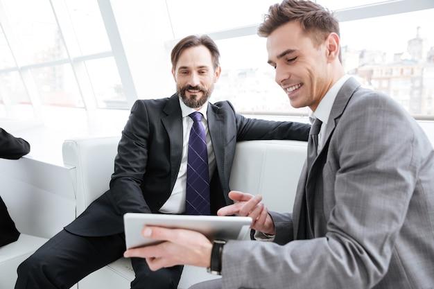 Dois parceiros de negócios conversando no escritório, sentados no sofá e olhando para o computador tablet