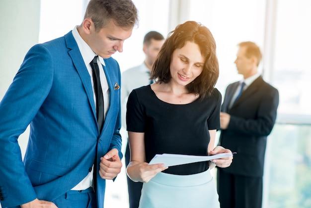 Dois parceiros de negócios, examinando o documento no escritório