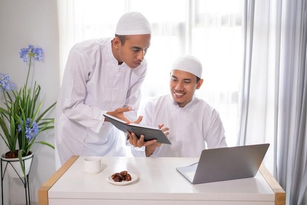 Dois parceiros de negócios muçulmanos discutindo e se encontrando usando um laptop juntos