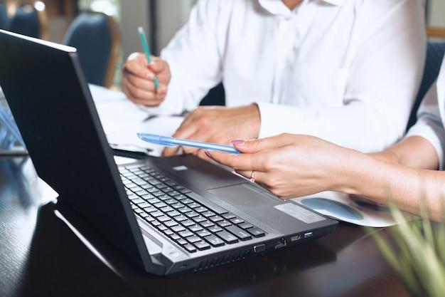 Dois parceiros de negócios, sentado em uma mesa juntos e trabalhando.