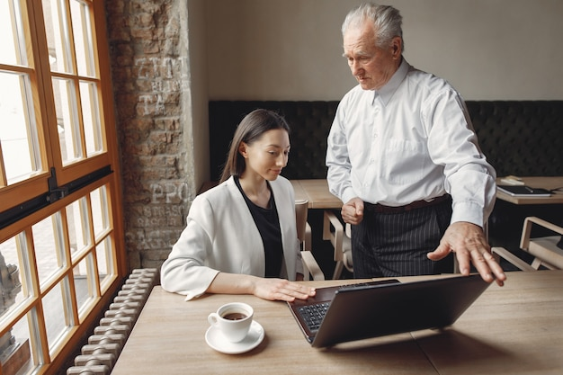 Dois parceiros de negócios, trabalhando com um laptop em um café