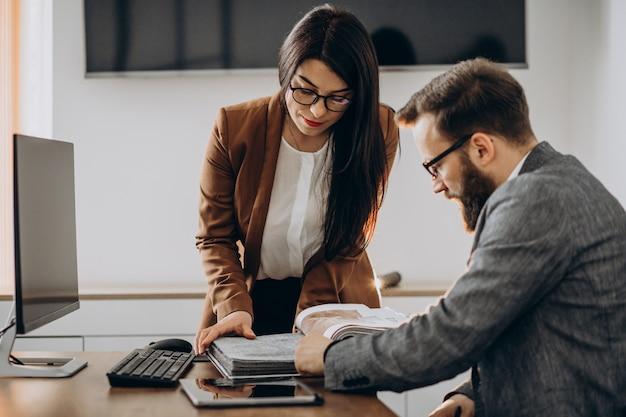 Dois parceiros de negócios trabalhando juntos no escritório no computador