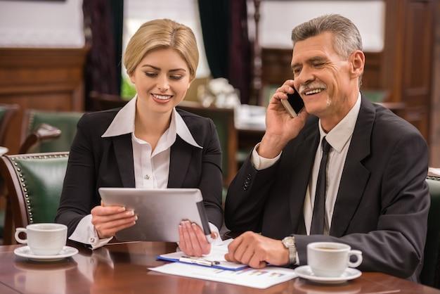 Dois parceiros de negócios usando o tablet digital.
